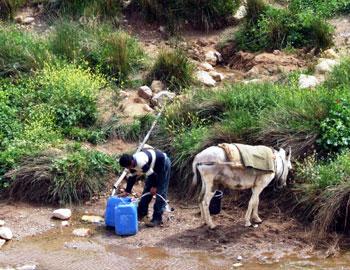 תושב כפר שאינו מחובר לרשת המים במחוז ג'נין ממלא מים ממעיין. צילום: עאטף אבו א-רוב, בצלם, 23.3.09.