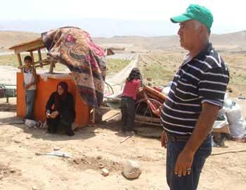 עלאן דר'ארמה ובני משפחתו תושבי אל-פארסייה ליד שיירי רכושם. צילום: עאטף אבו א-רוב, בצלם, 10.8.10.