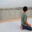 <p>[4859]  صبي ينظر الى الجدار الفاصل الذي عزل منزله عن باقي منازل قرية مسحة</p><p>تصوير: ايال دور</p>