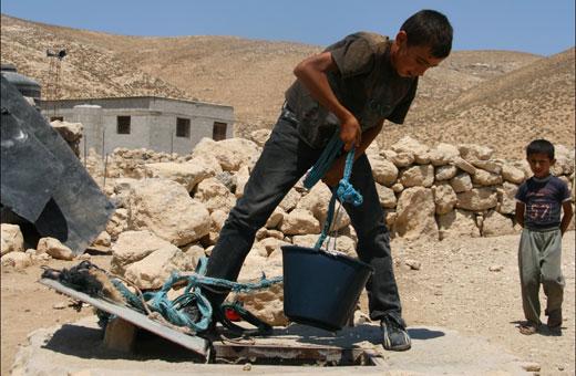 Palestinian boy drawing water from a cistern, Khirbet Jenbah, South Hebron Hills, 7 August 2012. Photo: Sharon Azran, B'Tselem. . צילום: שרון עזרן, בצלם