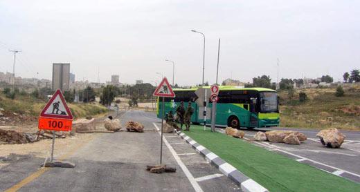 Settler bus drives through Beitin Road, while army blocks Palestinian traffic once again. Photo: Iyad Haddad, B'Tselem 26.5.2015