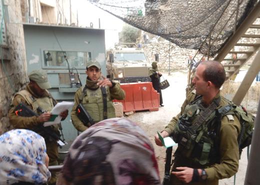 Checking residents' names at Bab a-Zawiya Checkpoint, Tel Rumeidah. Photo by Musa Abu Hashhash, B'Tselem, 5 Nov. 2015