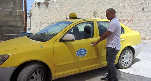 Ahmed Ali Ahmad next to his taxi. Photo by Abdulkarim Sadi, B'Tselem, 28 Sept 2017